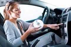 Weiblicher Treiber, der Musik im Auto spielt Stockfotos