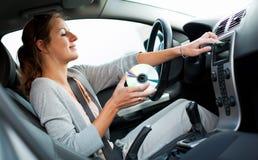Weiblicher Treiber, der Musik im Auto spielt Lizenzfreie Stockfotografie
