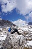 Weiblicher Trekker, der auf dem Felsen mit schöner Landschaftsrückseite sitzt Stockbilder