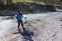 Weiblicher Trekker, der am Rand des Flusses steht Stockfoto