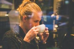Weiblicher trinkender Latte im Café lizenzfreies stockfoto