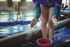 Weiblicher Turner, der Kreidepulver auf ihren Händen bevor dem Üben anwendet stockbild