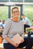Weiblicher Tutor Sitting In Classroom mit Digital-Tablet Lizenzfreie Stockfotografie