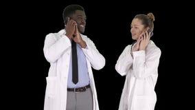 Weiblicher und m?nnlicher Doktor unter Verwendung der Handys, welche die Anrufe sagen gl?cklichen Nachrichten, Alpha Channel mach stock video footage