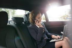 Weiblicher Unternehmer, der während des Reisens zum Büro arbeitet Lizenzfreie Stockfotografie