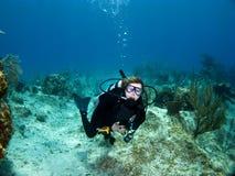 Weiblicher Unterwasseratemgerät-Taucher, der die Kamera betrachtet Stockfotografie