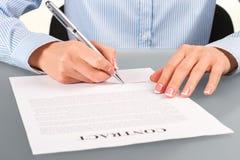 Weiblicher unterzeichnender Vertrag am Schreibtisch Lizenzfreie Stockbilder