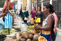 Weiblicher Verkäufer der Straße, der Bananen und Kokosnuss in Cartagena verkauft Stockfotografie
