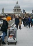 Weiblicher Verkäufer junger Cameralised-Erdnuss London-` s an der Jahrtausend-Brücke, die St- Paul` s Kathedrale übersieht Stockbild
