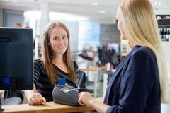 Weiblicher Verkaufs-Sekretär At Counter Lizenzfreies Stockfoto