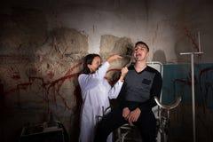 Weiblicher Verrücktheitswissenschaftler, der medizinische Zange vor Klaps hält Stockfoto