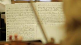 Weiblicher Violinist spielt Violine an einem Konzert der klassischen Musik gegen Anmerkungsblatt stock footage