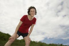 Weiblicher Wanderer auf Wiese gegen Wolken Stockfotografie