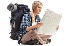 Weiblicher Wanderer, der auf dem Boden sitzt und eine generische Karte betrachtet Stockbild