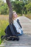 Weiblicher Wanderer, der auf hölzernem Weg in der Natur sitzt Lizenzfreies Stockfoto