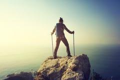 weiblicher Wanderer, der auf Sonnenaufgangküsten-Klippenrand steht Lizenzfreie Stockfotografie