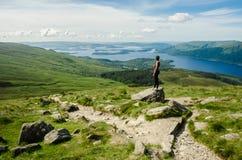 Weiblicher Wanderer, der die Landschaft auf einem Weg führt zu die Spitze bewundert lizenzfreies stockbild