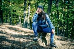 Weiblicher Wanderer, der im Wald sitzt Stockfoto