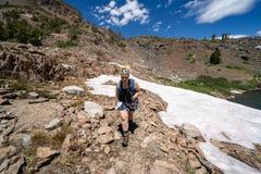 Weiblicher Wanderer, der nachdem dem Wandern durch ein kleines Schneefeld beunruhigt schaut lizenzfreie stockfotografie