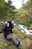 Weiblicher Wanderer nahe dem Fluss, der vom Regen schützt Stockfoto
