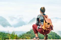 Weiblicher Wanderer sitzt am Rand der Straße und betrachtet ein mountai stockbild