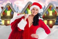 Weiblicher Weihnachtsmann, der einen Weihnachtsgeschenksack erzeugte hält digital, Hintergrund Stockbilder