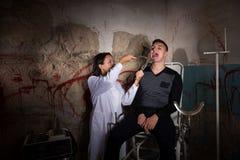 Weiblicher Wissenschaftler, der medizinische Zange vor Patienten hält und Lizenzfreies Stockbild