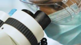 Weiblicher Wissenschaftler der Mischrasse, der sorgfältig Forschung unter Mikroskop, Nahaufnahme tut stock video