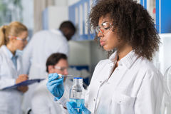 Weiblicher wissenschaftlicher Forscher In Laboratory, Afroamerikaner-Frau, die mit Flasche über Gruppe des Wissenschaftlers Makin lizenzfreies stockfoto