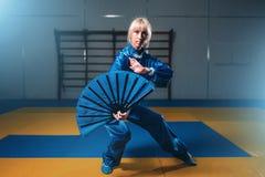 Weiblicher wushu Meister mit Fan, Kampfkünste Stockfotografie