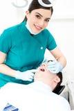 Weiblicher Zahnarzt überprüft einen Patienten lizenzfreie stockbilder