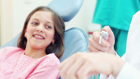 Weiblicher Zahnarzt, der einem kleinen Mädchen zahnmedizinische Instrumente zeigt stock video footage
