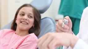 Weiblicher Zahnarzt, der einem kleinen Mädchen zahnmedizinische Instrumente zeigt stock video