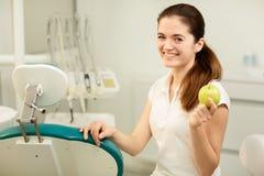Weiblicher Zahnarzt, der einen gr?nen Apfel, einen Zahnpflegen und ein Verhinderungskonzept l?chelt und h?lt stockbilder