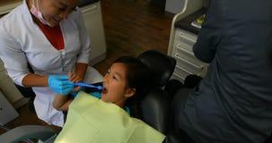 Weiblicher Zahnarzt, der einen Mädchenpatienten 4k überprüft stock footage