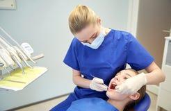 Weiblicher Zahnarzt, der geduldige Mädchenzähne überprüft stockbilder
