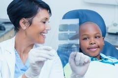 Weiblicher Zahnarzt, der Jungen seinen Mundröntgenstrahl zeigt Stockfoto