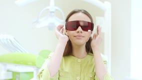 Weiblicher Zahnarzt, der oben ultraviolette orange Sicherheitsschutzbrillen kleidet Auf einem weißen Hintergrund stock video footage