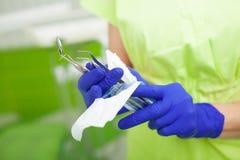 Weiblicher Zahnarzt nehmen die zahnmedizinischen Werkzeuge, die in einer Schutzfolie verpackt werden lizenzfreie stockbilder