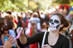 Weiblicher Zombie teilt Süßigkeit an Halloween-Parade aus Stockfoto