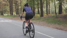 Weibliches aktives sportives Radfahrerreitfahrrad im Park Radfahrentraining Fahrradfahrt Langsame Bewegung stock footage