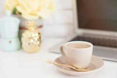 Weibliches Arbeitsplatzkonzept Bequemer Weiblichkeitsarbeitsplatz der freiberuflich tätigen Mode mit Laptop, Kaffee, Blumen, gold Stockfotos