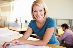 Weibliches Architekten-Studying Plans In-Büro Lizenzfreies Stockfoto