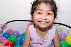 Weibliches asiatisches Kindermädchen beim Sitzen und Spielen mit bunten Plastikbällen stockbild