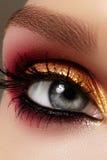 Weibliches Auge der Nahaufnahme mit hellem Make-up der Mode Schönes Gold, roter Lidschatten, Funkeln, schwarzer Eyeliner Form-Aug Stockbilder