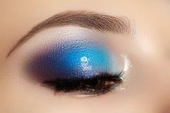 Weibliches Auge der Nahaufnahme mit hellem Make-up der schönen Mode Schöner glänzender blauer Lidschatten, machte Funkeln, schwar Lizenzfreies Stockfoto