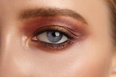 Weibliches Auge der Nahaufnahme mit hellem rotem Make-up Stockbild