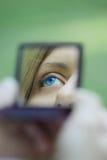 Weibliches Auge reflektiert in einem Taschenspiegel Lizenzfreie Stockfotos