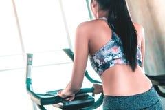 Weibliches Ausarbeiten auf Schrittbergsteigermaschine in der Eignungsturnhalle für gesundes Lebensstilkonzept, Ansicht von hinten stockfotos