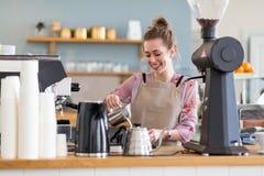 Weibliches barista, das Kaffee macht stockfotos